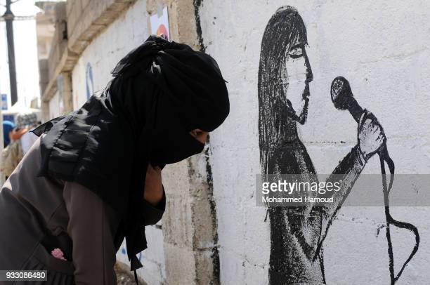 Yemeni woman draws graffiti during an Open Day of graffiti campaign call for peace on March 15, 2018 in Sana'a, Yemen.