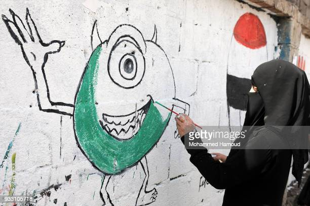 A Yemeni woman draws graffiti during an Open Day of graffiti campaign call for peace on March 15 2018 in Sana'a Yemen