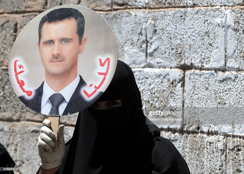 A Yemeni woman holds a photo of Syrian President Bashar al-Assad during a protest against U.S. allied missile strikes against Syria outside the Syrian embassy on April 16, 2018 in Sana'a, Yemen. The U.S., Great Britain and France launched missile strikes in response to the Syrian goverment using chemical weapons against its own population.