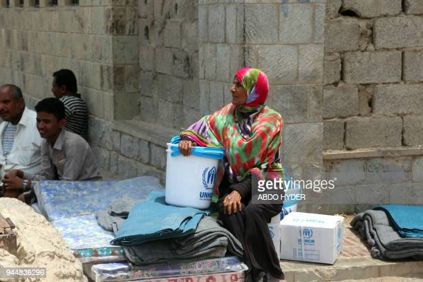 A Yemeni woman sits next to blankets and upholstery distributed by the UN High Commissioner for Refugees to those affected by the conflict in the...