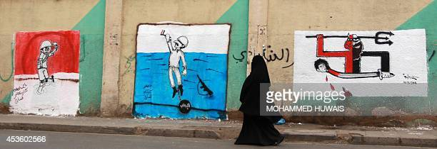 A Yemeni woman walks past murals denouncing the recent abduction and execution of 15 Yemeni soldiers by AlQaeda militants on August 14 2014 in the...