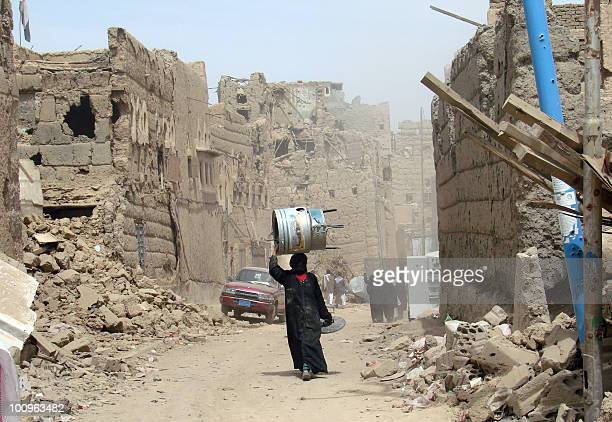 A Yemeni woman walks through a heavily damaged neighbourhood in the warbattered city of Saada 240 kms north of the Yemeni capital Sanaa on March 8...