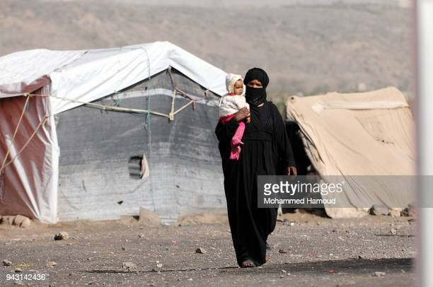 A Yemeni woman who fled her home due to the ongoing war walks as she carries her baby outside her makeshift shelter at an internally displaced camp...