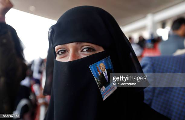 A Yemeni woman with a portrait of Yemen's expresident Ali Abdullah Saleh attached to her niqab attends a rally in support of the former president as...
