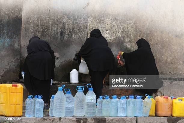 Yemeni women fill their jerrycans with clean water from a charity pump during a continuing clean water crisis on July 24, 2018 in Sana'a, Yemen.