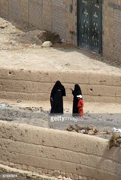 Yemeni women walk with a child though a damaged neighbourhood in the warbattered city of Saada 240 kms north of the Yemeni capital Sanaa on March 8...