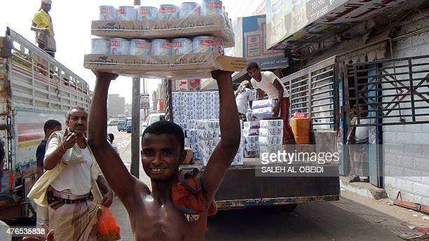 A Yemeni worker carries tins as people unload a truck on June 10 2015 in the port city of Aden Yemen faces lack of goods and a rise of level of...