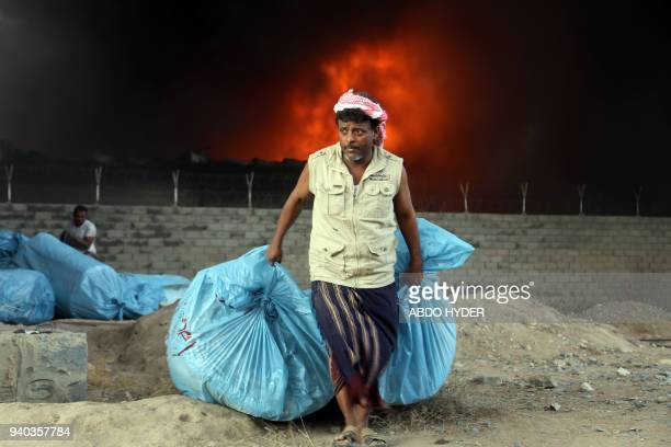 A Yemeni worker evacuates food bags as fire engulfs the United Nations' World Food Programme's warehouse in the coastal town of Hodeida on March 31...