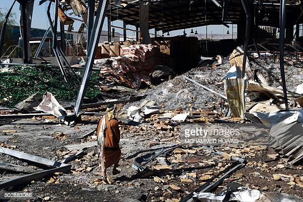 A Yemeni worker inspects the damage at a CocaCola factory after it was reportedly destroyed by Saudiled airstrikes in the capital Sanaa on December...