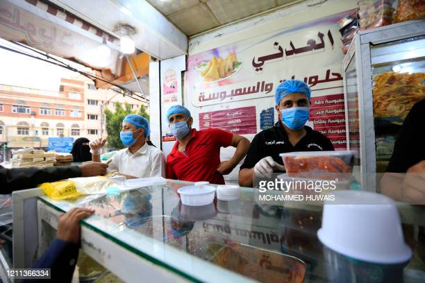 Yemeni workers clad in head caps and protective masks take orders from clients at a snack shop selling samosas known locally as sambusa in Sanaa late...