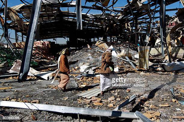 TOPSHOT Yemeni workers inspect the damage at a CocaCola factory after it was reportedly destroyed by Saudiled airstrikes in the capital Sanaa on...