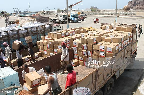Yemeni workers unload medical aid boxes from a boat carrying 460 tonnes of Emirati relief aid that docked in the port of the city of Aden into a...