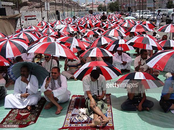 Yemeni worshipers hold their sun umbrellas depicting their national flag as they listen to the Friday prayers sermon in the southern city of Aden on...