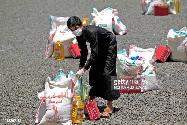 Yemeni youth carries a portion of food aid, distributed by Yadon Tabney development foundation, in Yemen's capital Sanaa on May 17, 2020.