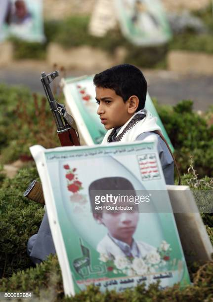 A Yemeni youth carrying a gun sits next to a grave in a cemetery in the capital Sana on June 25 2017 after the Eid alFitr prayer which marks the end...