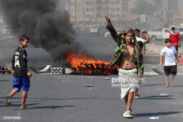 A Yemeni youth flashes the V for victory sign near burning tyres as protesters demonstrate against inflation and the rise of living costs in the...