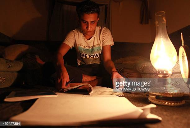 A Yemeni youth reviews his studies for the final exams on the light of an oil lamp in Sanaa late on June 10 2014 Yemen suffered a total blackout...