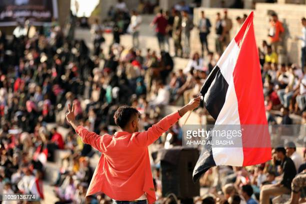 A Yemeni youth waves a national flag during a celebration marking the 56th anniversary of the 1962 revolution which established the Yemeni republic...