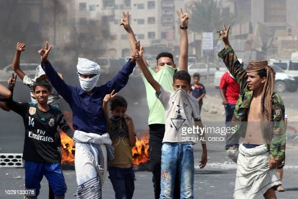 Yemeni youths flash the V for victory sign near burning tyres as protesters demonstrate against inflation and the rise of living costs in the...