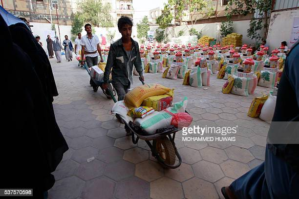 Yemenis affected by the country's ongoing conflict receive food rations provided by an initiative organised by a local charity in the capital Sanaa...