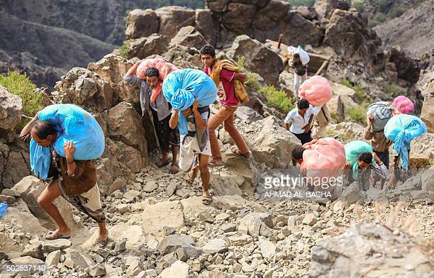 Yemenis carry food parcels as they walk through the mountains along the only path accessible between the southern cities of Aden and Taez on December...
