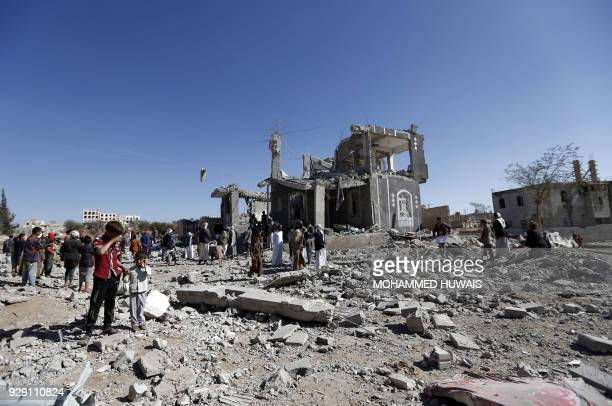 TOPSHOT Yemenis check the damage in the aftermath of a reported air strike by the Saudiled coalition in the Yemeni capital Sanaa on March 8 2018 /...