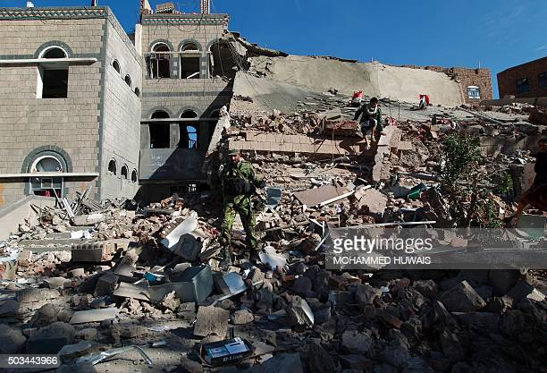 Yemenis check the rubble of the building of the Chamber of Commerce and Industry which was destroyed during air strikes on the capital Sanaa on...