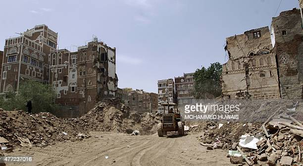 Yemenis clear the rubble of houses in the UNESCO-listed heritage site in the old city of Yemeni capital Sanaa, on June 15, 2015. UNESCO condemned the...