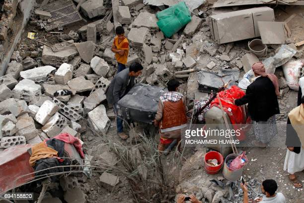 Yemenis collect belongings from the rubble of houses destroyed in a suspected Saudiled coalition air strike in Sanaa on June 9 2017 Four civilians...