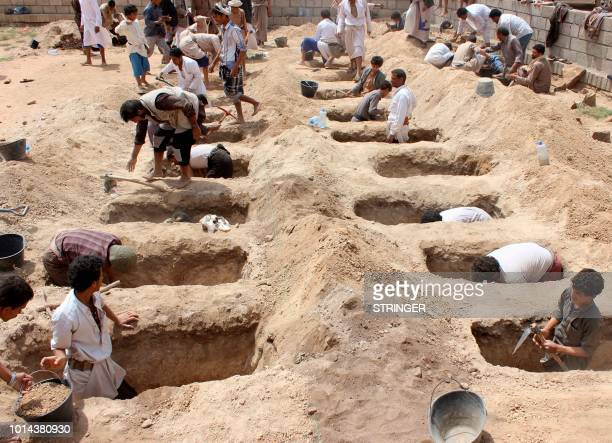 TOPSHOT Yemenis dig graves for children who where killed when their bus was hit during a Saudiled coalition air strike that targeted the Dahyan...