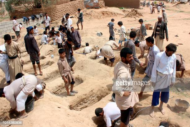Yemenis dig graves for children who where killed when their bus was hit during a Saudiled coalition air strike that targeted the Dahyan market the...