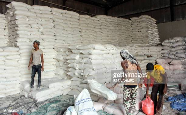 Yemenis distribute sacks of food aid to be given to displaced people who fled battles in the Red Sea province of Hodeida and are now living in camps...