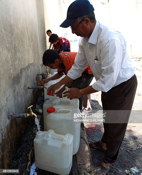 Yemenis fill plastic jerry cans with water at a public tap on April 12 2014 at a slum in the capital Sanaa Yemen ravaged by years of factional strife...