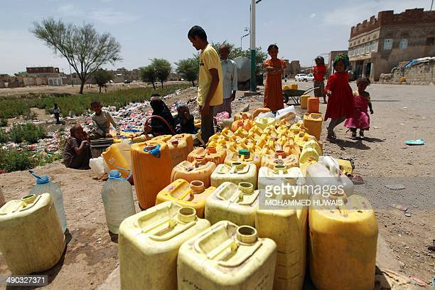 S 'THE WORLD'S WATER' PACKAGE Yemenis fill plastic jerry cans with water at a public tap on May 9 2014 at a slum in the capital Sanaa In the...