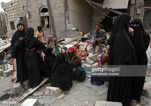 Yemenis gather amid the ruins of a building damaged in an airstrike by the Saudiled coalition on the capital Sanaa on July 13 2015 Air strikes in...