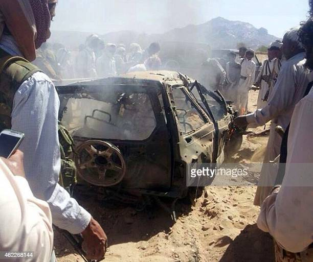 Yemenis gather around a burnt car after it was targeted by a drone strike killing three suspected alQaeda militants on January 26 2015 between the...