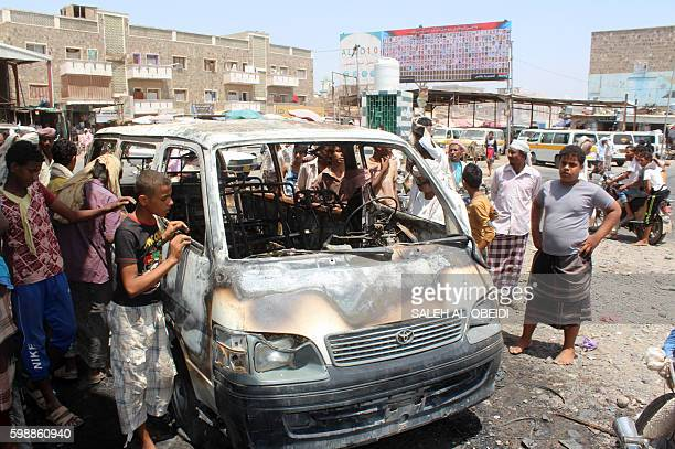 Yemenis gather around a burnt vehicle at the site where a mine that Yemeni soldiers were taking away in their vehicle blew up in a marketplace on...
