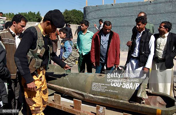 Yemenis gather around the remains of a rocket during a protest in front of the United Nations office calling for an end to the military operations...