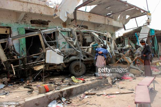 Yemenis gather next to the destroyed bus at the site of a Saudiled coalition air strike that targeted the Dahyan market the previous day in the Huthi...