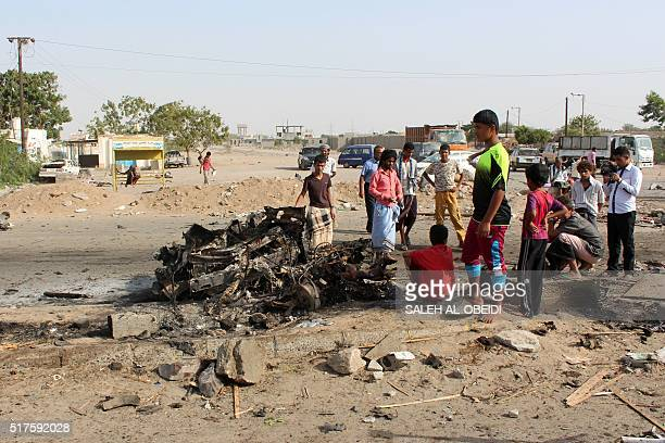 Yemenis gather on March 26 2016 at the site of a suicide bomb attack that struck the day before checkpoints of Yemeni loyalist forces in Shaab...