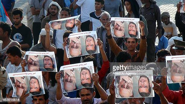 Yemenis hold a crossed out posters of Yemeni president Ali Abdullah Saleh and leader of Houthis AbdulMalik alHouthi during a rally against the...