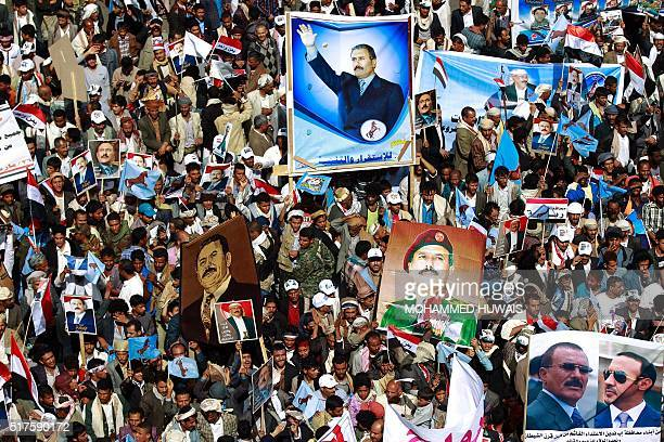 TOPSHOT Yemenis hold placards bearing portraits of former president Ali Abdullah Saleh during a protest against the Saudiled coalition commemorating...