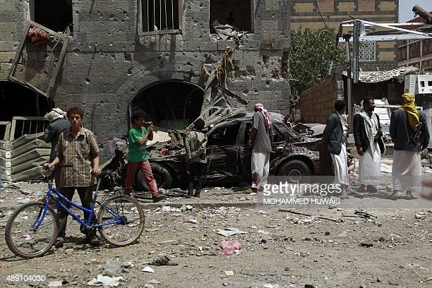 Yemenis inspect a burnt car following air strikes carried out by the Saudiled coalition in the capital Sanaa on September 19 2015 Air raids by...