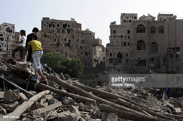 Yemenis inspect an area after a Saudiled coalition airstrike targeting Houthicontrolled residential areas in Babul Yemen area of Sanaa Yemen on...