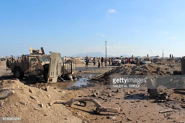 Yemenis inspect the damage after a suicide bomber rammed his explosivesladen vehicle into an area where security forces and progovernment militiamen...