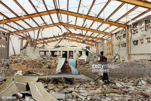 Yemenis inspect the damage caused by a Saudiled air strike on a cholera treatment centrer supported by Doctors Without Borders in the Abs region of...
