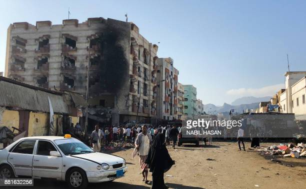 Yemenis inspect the site of a suicide bombing that targeted the finance ministry building of the Saudibacked Yemeni government in the country's...