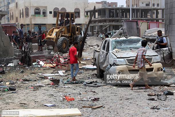 Yemenis inspect the site of a suicide car bombing claimed by the Islamic State group on August 29 2016 at an army recruitment centre in the southern...