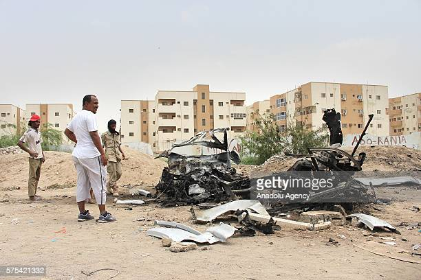 Yemenis inspect wreckage of a vehicle following a suicide car bombing that targeted Yemen's port city Aden's governor Aidarus alZubaid in Aden Yemen...