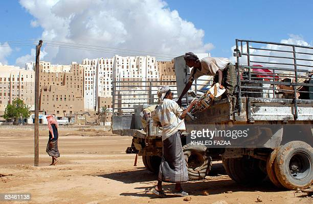 Yemenis load a truck with their processions after their home collapsed following storms in the historical city of Shibam in Hadramaut province of...